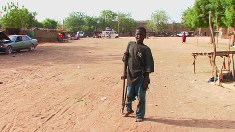 A boy walks on crutches in a poor African town Stock Video Footage