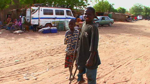 A boy walks on crutches in a poor African town Footage