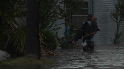 A man rescues a elderly citizen from flooding duri Footage