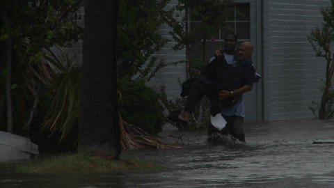 A man rescues a elderly citizen from flooding duri Stock Video Footage