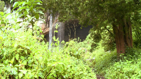 Backpackers approach a tropical waterfall Stock Video Footage