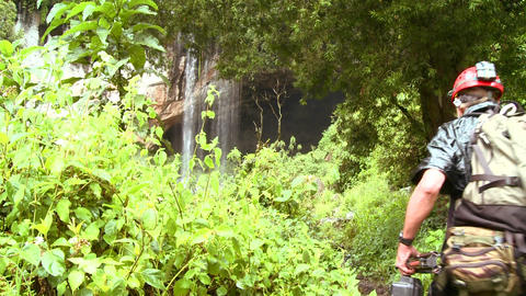 Backpackers approach a tropical waterfall Footage