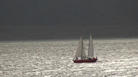 A sailboat travels on silvery water Footage