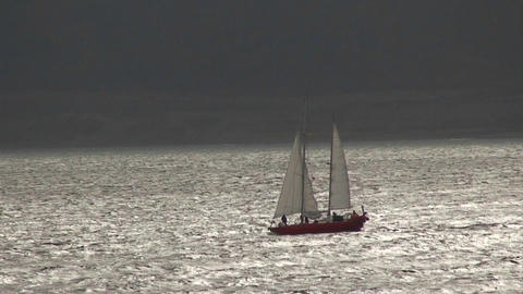 A sailboat travels on silvery water Stock Video Footage