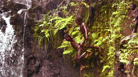 New Guinea children dive into a lake from a cliff Stock Video Footage