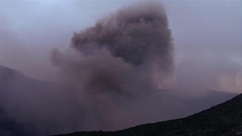 A volcano erupts in the distance Footage