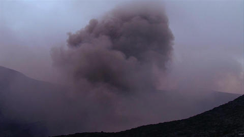 A volcano erupts in the distance Stock Video Footage