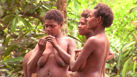 New Guinea women look on at a tribal dance perform Stock Video Footage