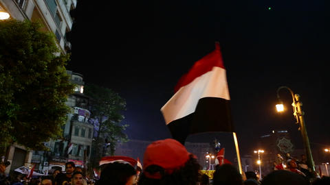 Flags wave above the crowd at a nighttime protest Stock Video Footage