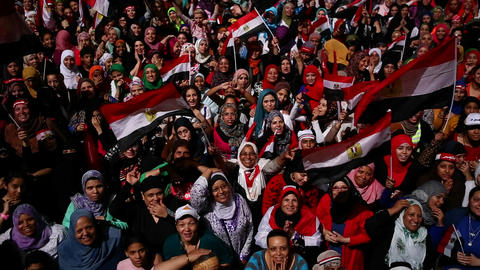 Protestors chant at a nighttime rally in Tahrir Sq Stock Video Footage