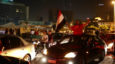 A man waves a flag from a car at a nighttime rally Stock Video Footage
