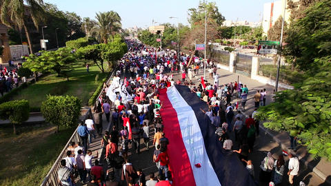 Protestors march and carry a large flag in Cairo,  Footage