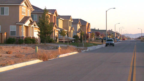 Tract homes line a street in a suburban sprawl com Footage