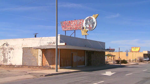 An abandoned liquor store sits in a modern ghost t Stock Video Footage