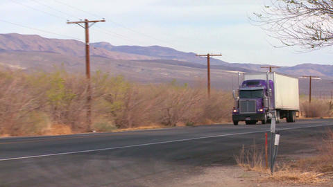 A long distance truck drives on a road through the Footage