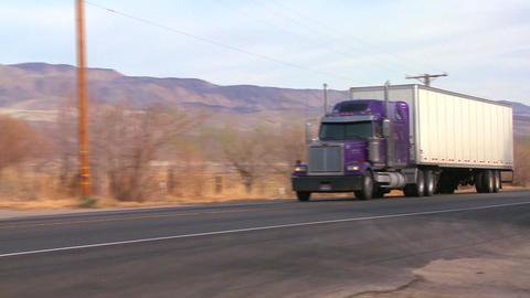 A long distance truck drives on a road through the Stock Video Footage