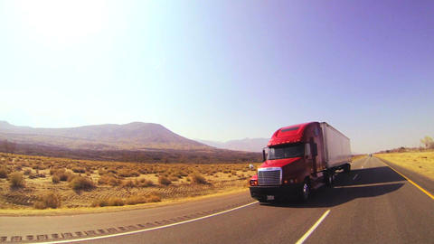 An 18 wheeler truck moves across the desert in thi Stock Video Footage