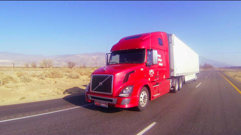 A red 18 wheeler truck moves across the desert in Stock Video Footage
