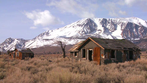 Abandoned settler cabins with the snowcapped Sierr Stock Video Footage
