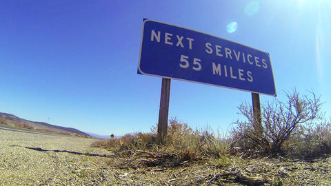 A sign on a lonely desert road warns that the next Stock Video Footage