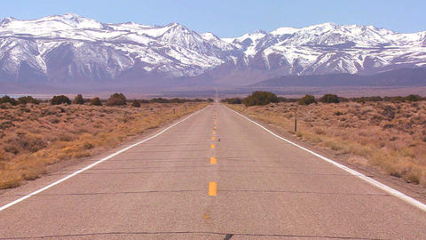 A long straight lonely road heads to the mountains Stock Video Footage