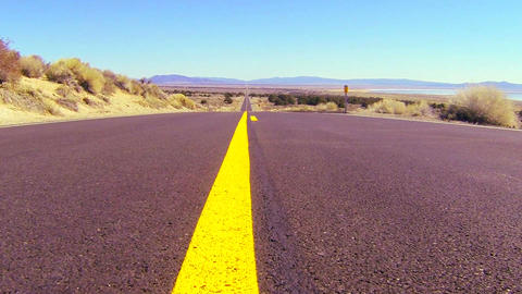 Dolly shot along an open road past the center line Footage