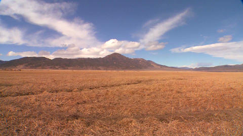 Clouds move over a distant mountain behind a field Footage