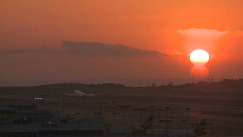 A plane takes off into the sunset or sunrise Footage