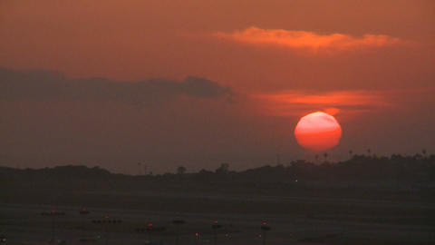 An orange ball of sun sets behind the LA hills Footage