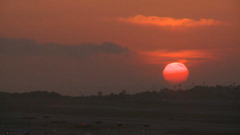 An orange ball of sun sets behind the LA hills Stock Video Footage
