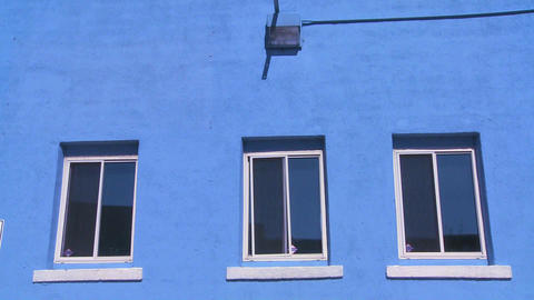 Blue windows look out from a blue building Stock Video Footage