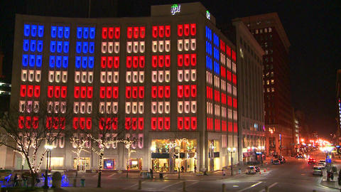 An office building is lit up at night with the Ame Stock Video Footage
