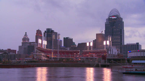 Nighttime falls over Cincinnati as riverboats pass Stock Video Footage