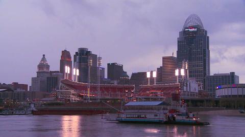 Nighttime falls over Cincinnati as riverboats pass Stock Video Footage
