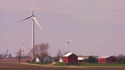Giant windmills generate power behind farms in the Stock Video Footage