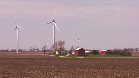 Giant windmills in the distance generate power beh Stock Video Footage
