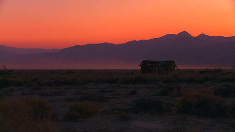 The sun sets behind an abandoned cabin the desert Stock Video Footage