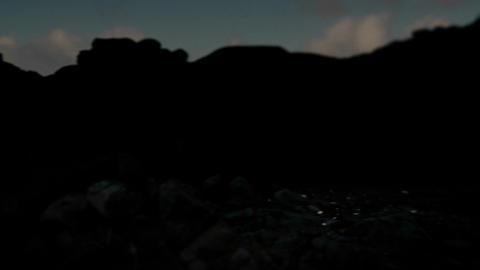 Pan across a darkened coastline to an ocean inlet Stock Video Footage