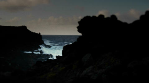 Pan across a darkened coastline to an ocean inlet Footage