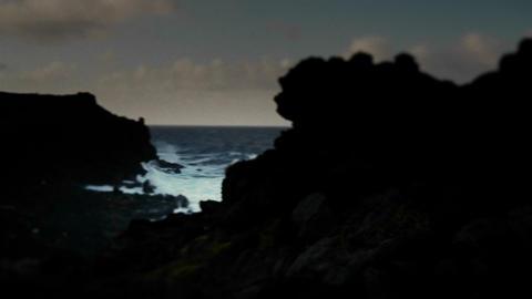 Pan across a darkened coastline to an ocean inlet Footage