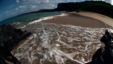 Ocean waves roll into a Hawaiian beach in this fis Stock Video Footage