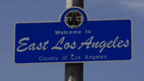 Rack focus on a Welcome to East Los Angeles sign a Live Action