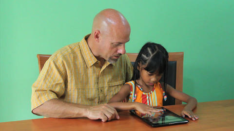 Asian Girl Learns How To Use Tablet With Father Stock Video Footage