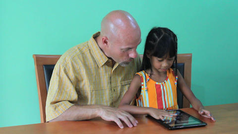 Father Helps Daughter Use Digital Tablet Footage