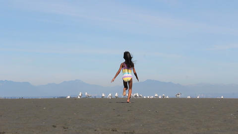 Asian Girl Chasing Down Birds On The Beach Footage