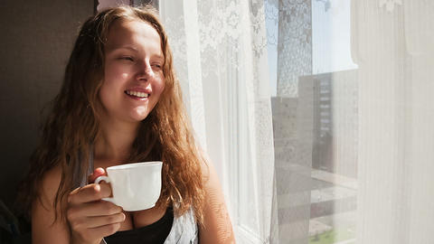 Woman at the window with a cup of coffee Stock Video Footage