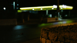 Gas station at night defocused cars passing by Stock Video Footage