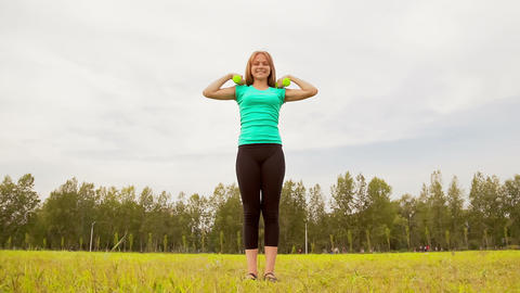 Woman with dumbbells in a meadow Stock Video Footage
