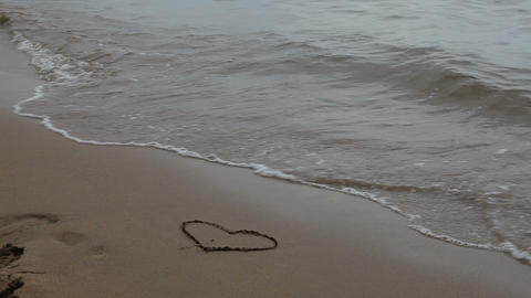 drawing a heart in the sand and then stomping on it Stock Video Footage