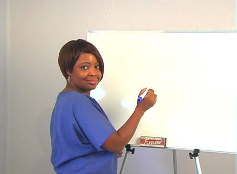 "Beautiful Nurse Writes ""Caesarean Section"" on a White Board Stock Video Footage"